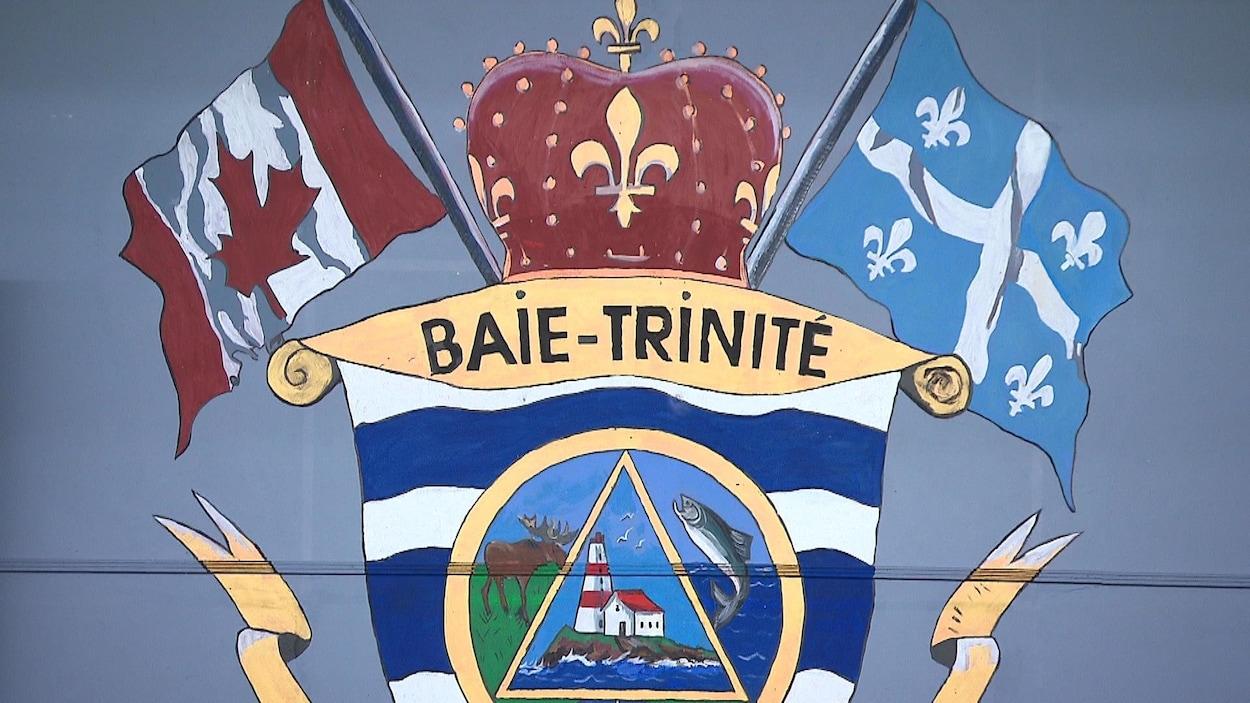 Les armoiries de la Municipalité du village de Baie-Trinité représentent les drapeaux du Canada et du Québec, un orignal, un poisson et un phare. Elles sont peintes sur un mur dans la salle de réunion.