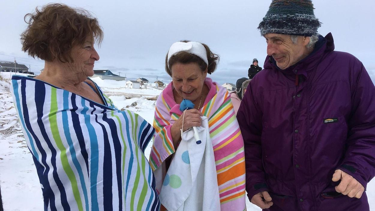 On voit deux femmes et un homme dehors, pendant l'hiver. Ils sont sur une plage recouverte de neige aux Îles-de-la-Madeleine. Les deux femmes sont enroulées dans des serviettes, car elles se sont jetées à l'eau dans le golfe du Saint-Laurent.