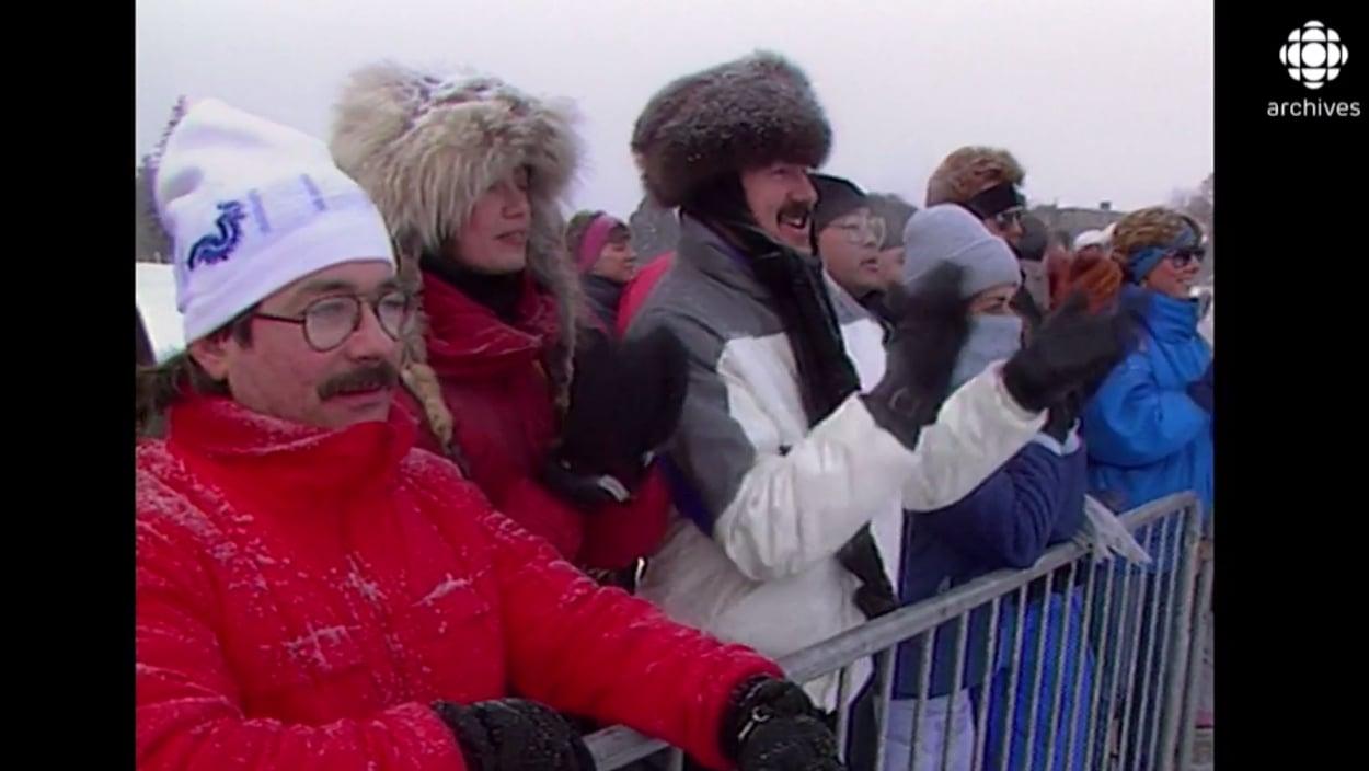 Des spectateurs, chaudement vêtus, assistent à une compétition sportive.
