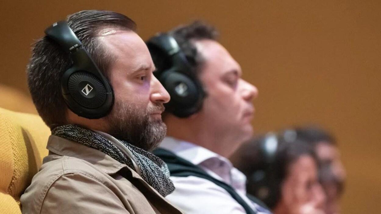 Deux hommes, avec des casques d'écoute, écoutent un balado.