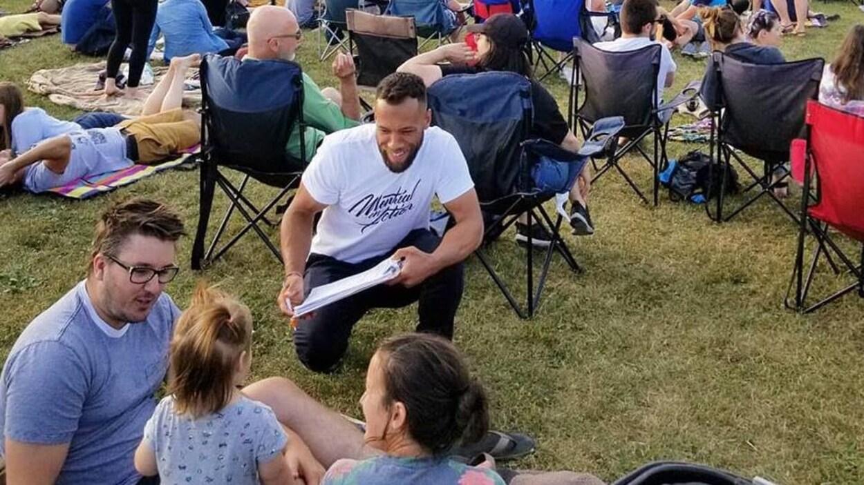 Un homme accroupi pour faire signer une pétition.