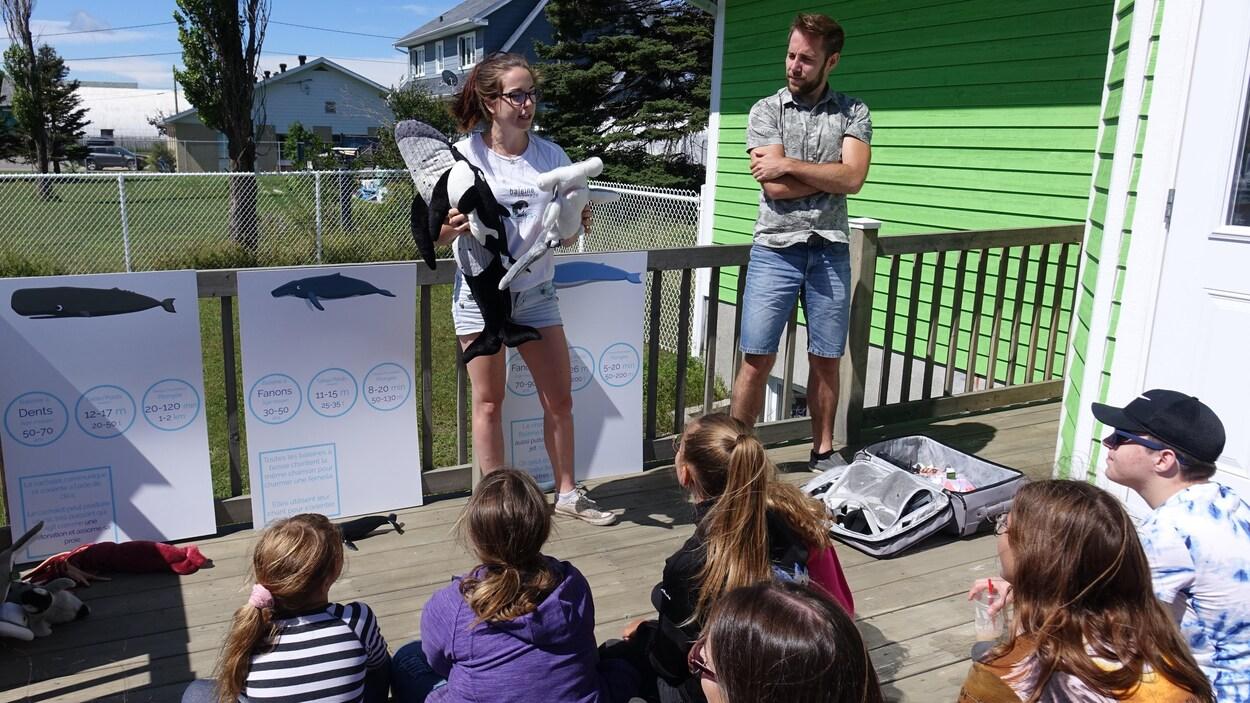 Vikie tient des peluches de baleine en s'adressant aux enfants assis devant elle.