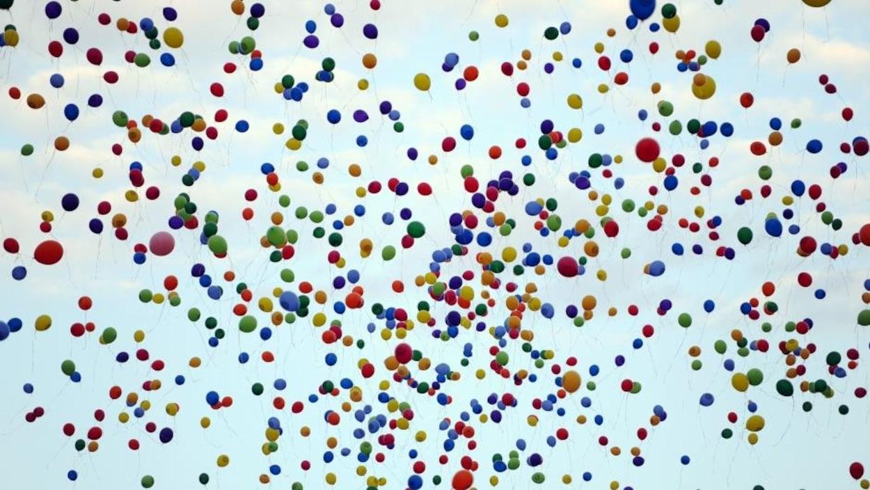 Une nuée de ballons gonflés à l'hélium dans le ciel.