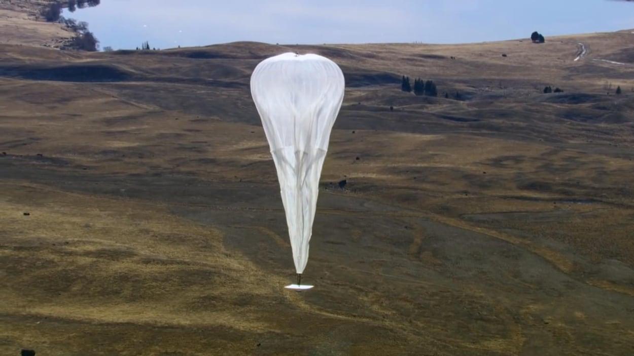 On voit un ballon servant aux télécommunications flotter dans les airs.