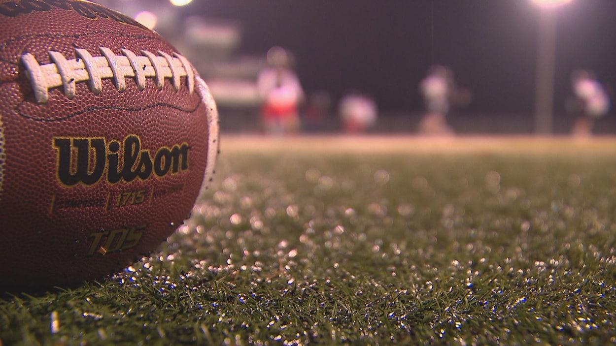 Ballon de football posé sur le sol, joueur flous à l'arrière-plan.