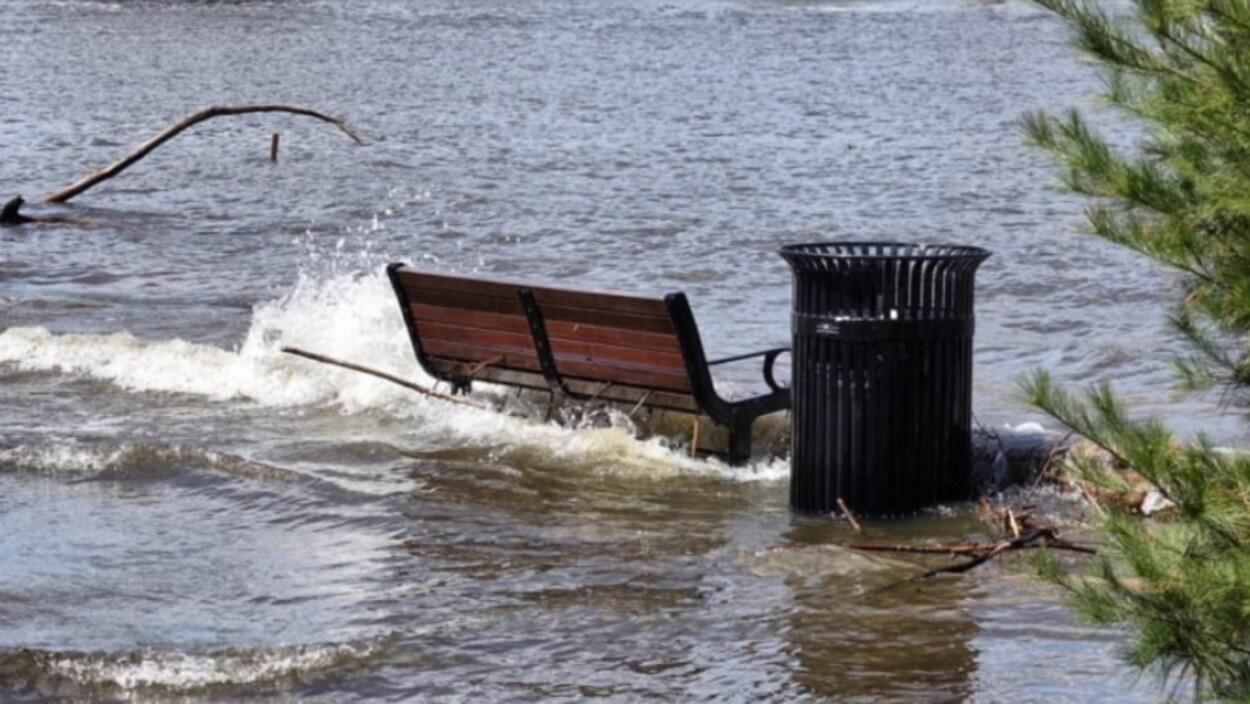 Un banc de parc et une poubelle entourés d'eau.
