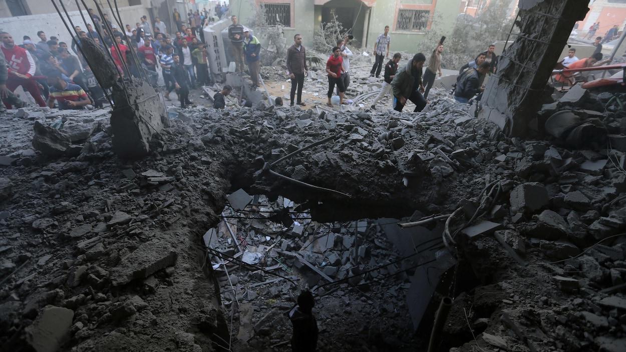 Des Palestiniens se rassemblent autour d'un bâtiment détruit par des bombardements israéliens.