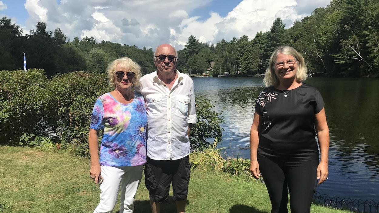 Trois personnes prennent la pose devant la rivière Magog, à Sherbrooke.
