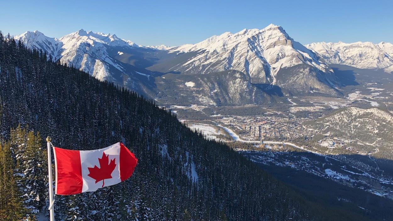 Vue de Banff du sommet du mont Sulphur, dans le parc national Banff. Un drapeau canadien flotte au premier plan.