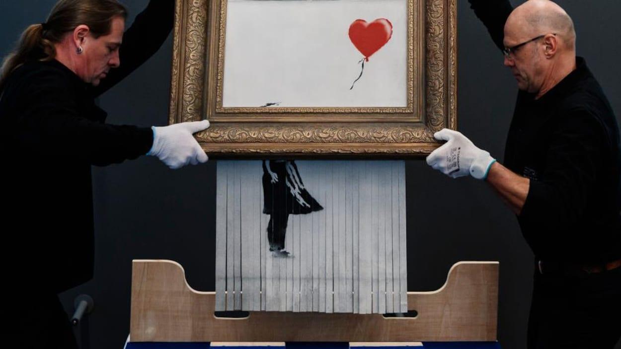 Deux hommes gantés de blanc soulèvent l'œuvre <em>Love is in the Bin</em> de Banksy pour la placer en exposition sur un mur du musée de Frieder Burda de Baden-Baden, en Allemagne.