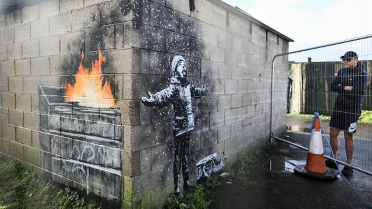 Un jeune garçon a les bras ouverts et respire des cendres d'un feu dans un conteneur.