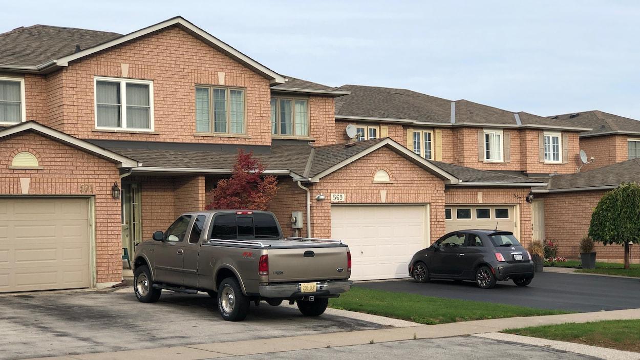 Des maisons en rangée à Burlington avec des voitures devant, en banlieue de Toronto.