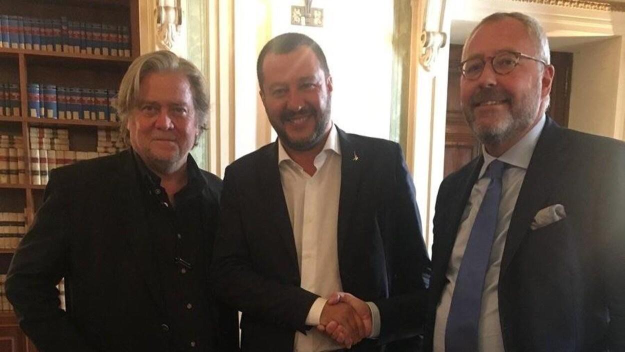 Trois hommes sont rassemblés dans une même pièce.