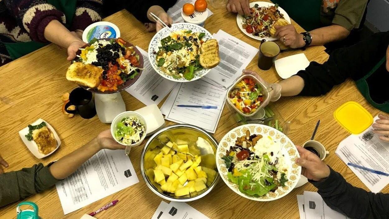 Des participants du programme Food Fit sont assis autour d'une table et mettent en évidence les mets qu'ils ont concocté.