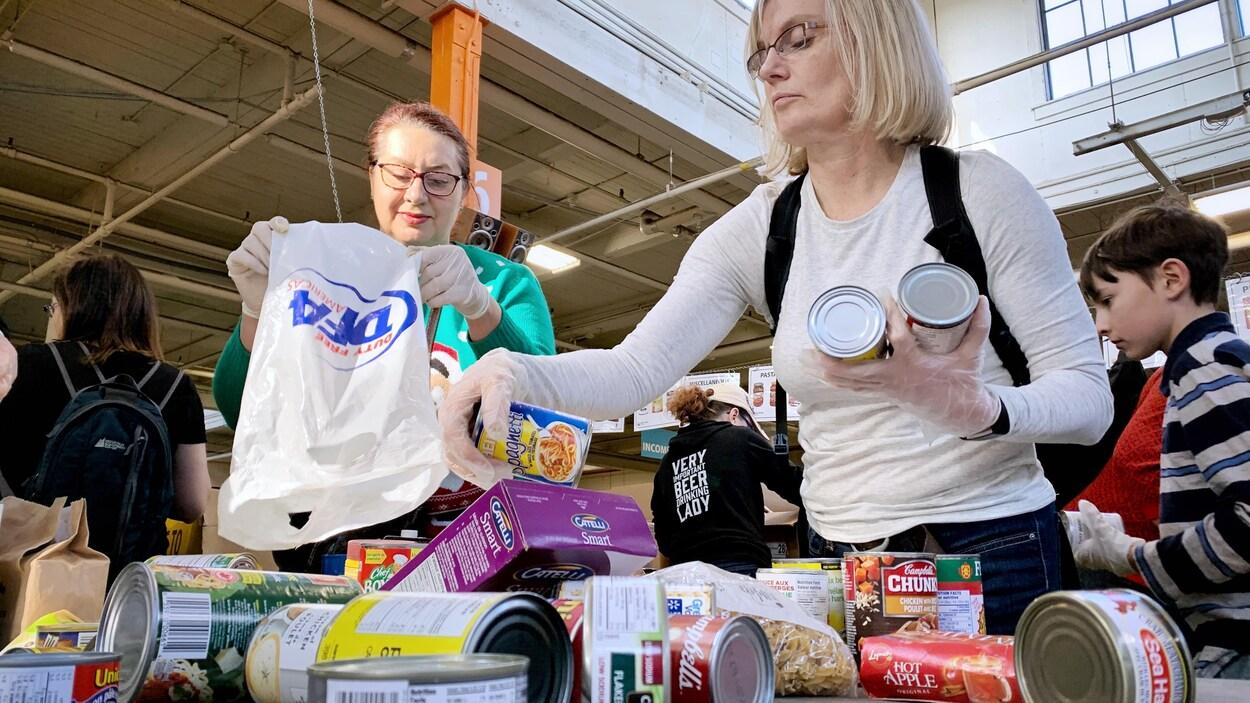Des bénévoles s'attellent à trier des boîtes de conserves et d'autres aliments.