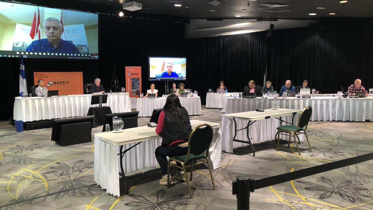 Une participante s'adresse aux experts du BAPE dans une salle.
