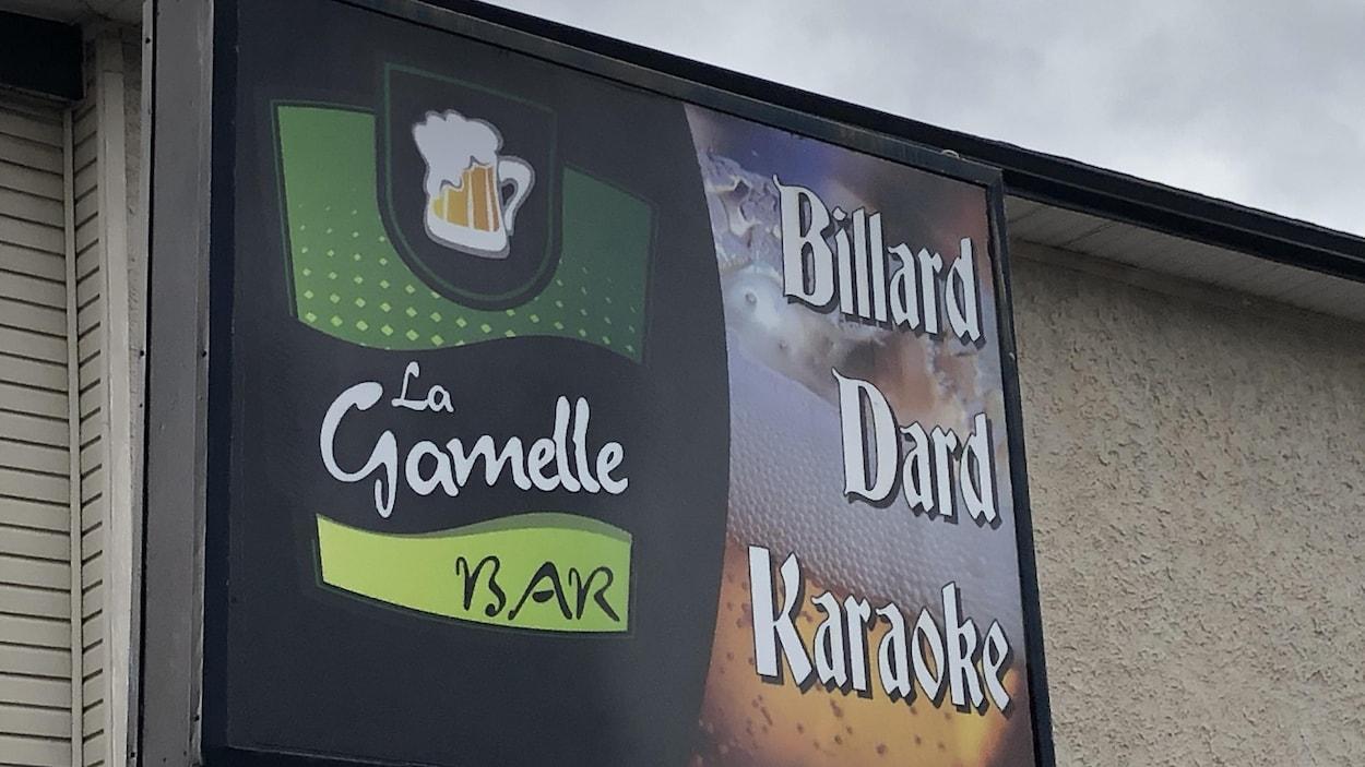 Enseigne du bar La Gamelle sur laquelle sont écrits les mots billard, dard et karaoké.