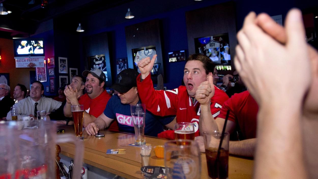 Un bar où sont rassemblés des partisans de hockey.