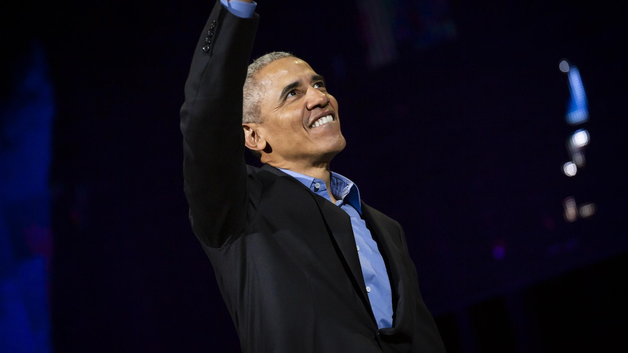 Barack Obama salue la foule, un bras dans les airs et un grand sourire aux lèvres.