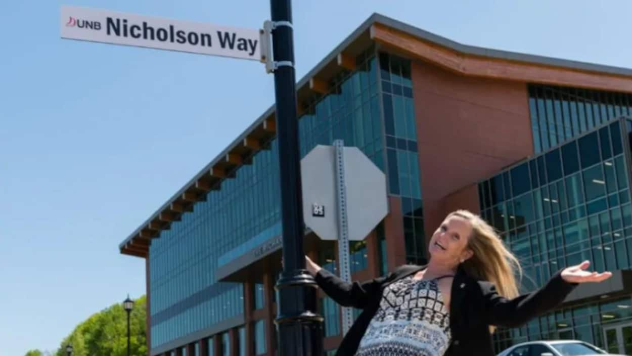 Barbara Nicholson qui s'accroche au poteau de la plaque de rue à son nom.