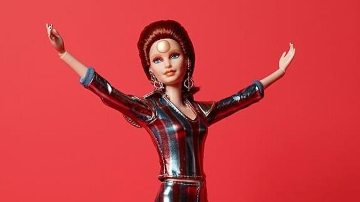 La poupée Barbie aux cheveux rouges a les bras ouverts.