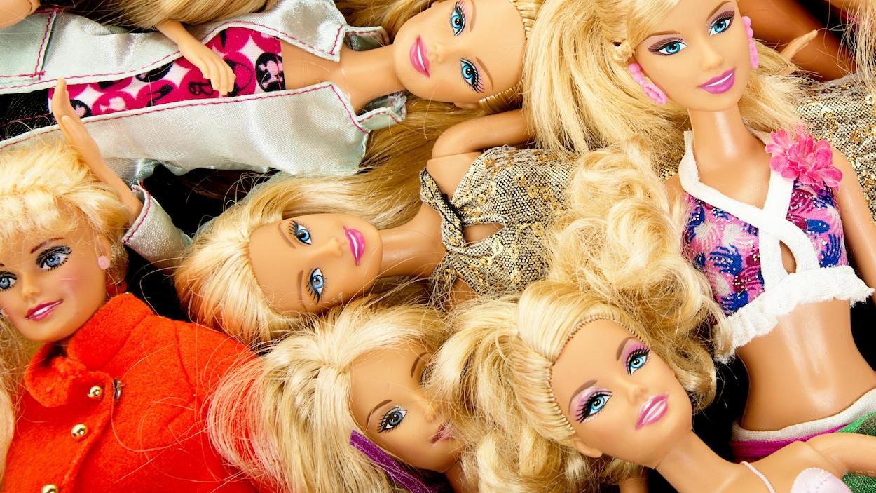 Une série de poupées Barbie couchées l'une sur l'autre.