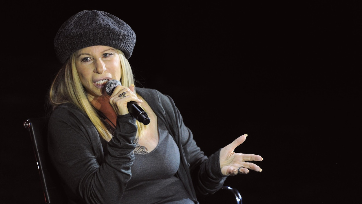 La chanteuse Barbra Streisand, toute vêtue de noir, parle dans un microphone lors d'une conférence.