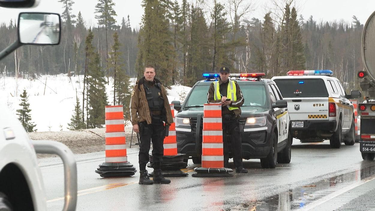 Deux policiers se tiennent debout devant leur véhicule et attendent qu'un camion s'arrête à côté d'eux.
