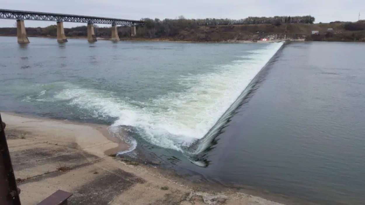 L'eau d'une rivière se déverse en aval d'un mur qui s'étend d'une rive à l'autre formant une zone de remous.