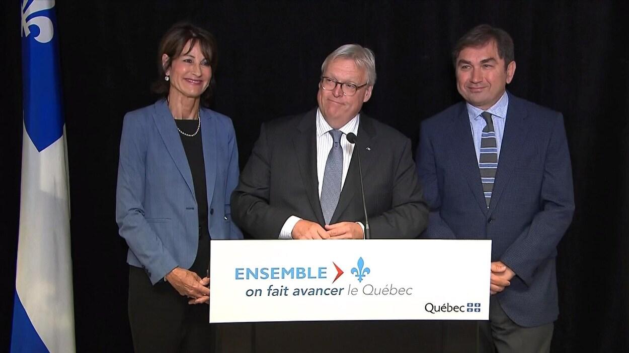 Les ministres Kathleen Weil et Gaétan Barrette et le Dr Mark Roper annonçant la création de la superclinique Reine Elizabeth dans l'arrondissement Notre-Dame-de-Grâce à Montréal