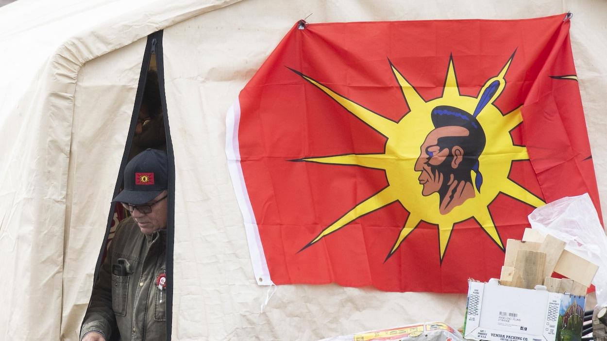 Un homme sort d'une tente à laquelle est accroché un drapeau mohawk.