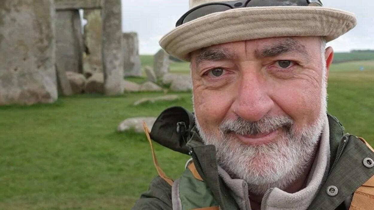 Un homme devant un monument en pierre.