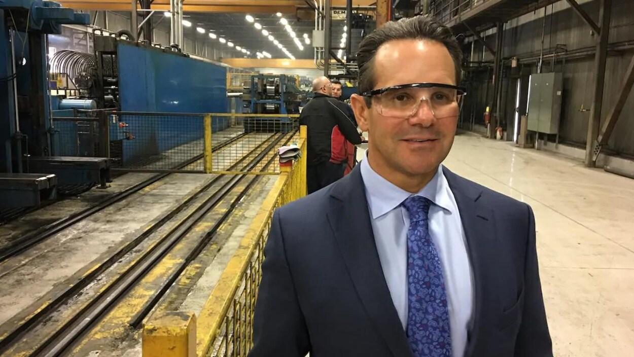 Un homme avec des lunettes de protection se trouve dans une usine.