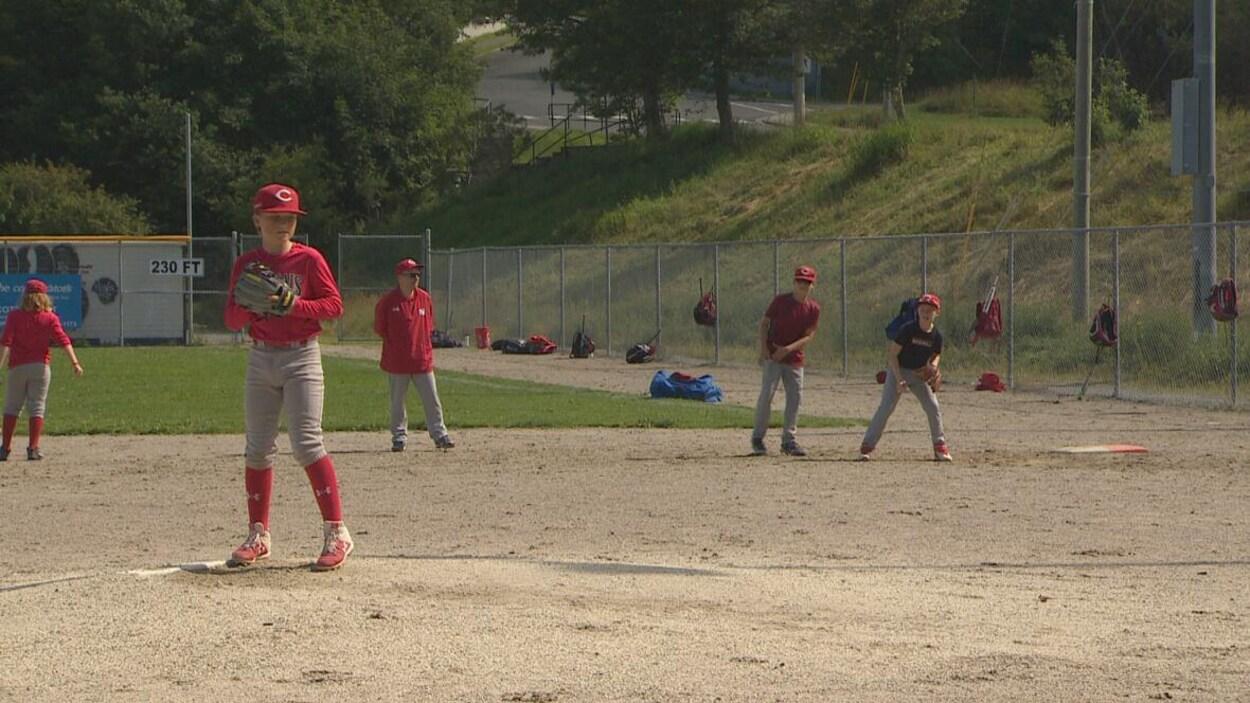 De jeunes joueurs de baseball sur un terrain.