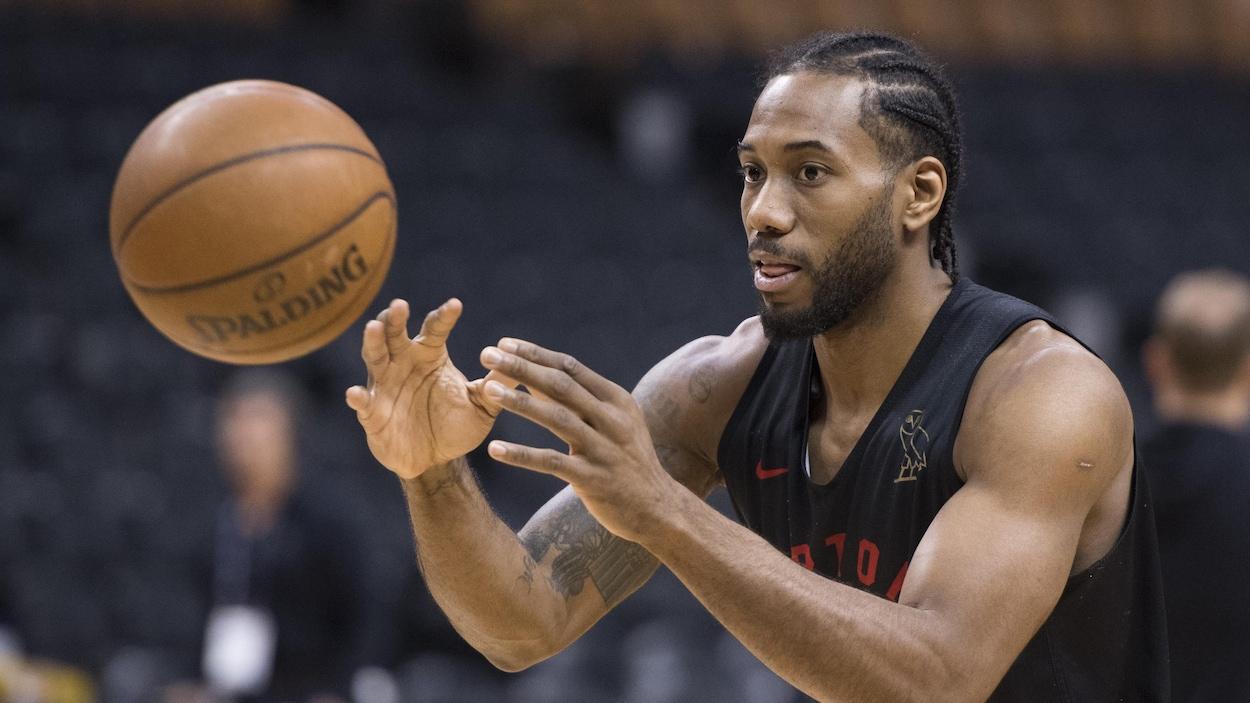 Photo d'un homme en maillot noir qui se prépare à attraper un ballon de basketball.