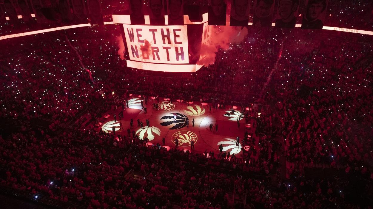 Dans l'aréna plongée dans l'obscurité et des lumières rouges, l'écran géant au centre et au dessus du terrain affiche le slogan We the North.