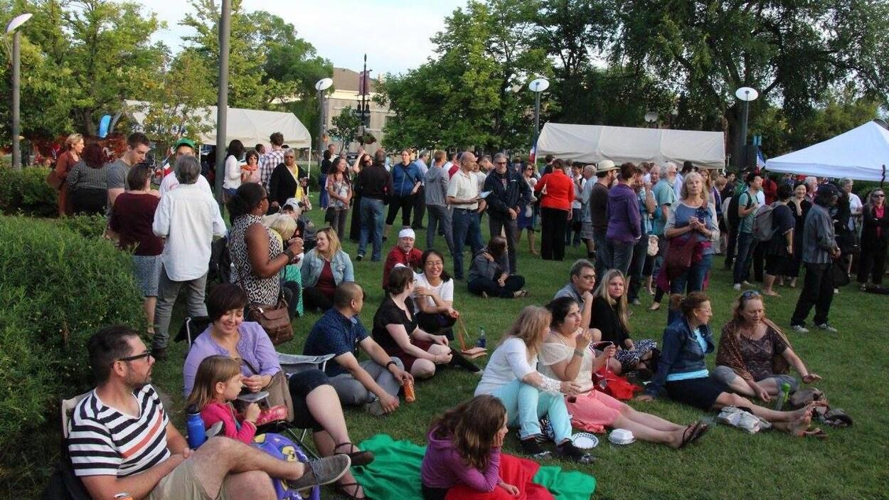 Des dizaines de personnes assises sur une pelouse ou debout près de tentes.