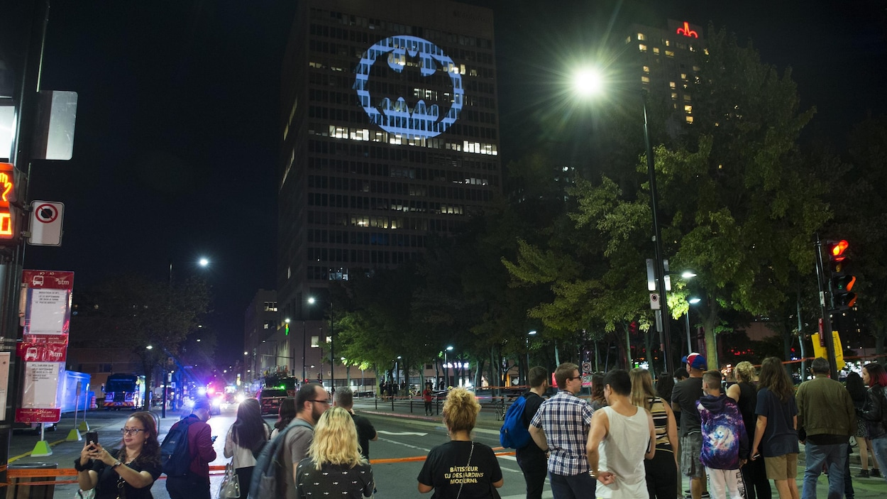 Des passants observent le Bat Signal projeté sur la façade d'un bâtiment du centre-ville de Montréal.