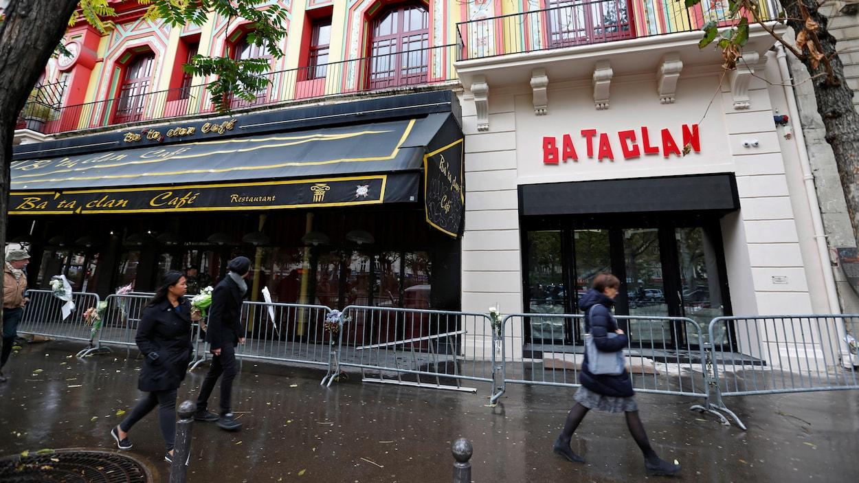 À Paris, des passants marchent devant le Bataclan, un an après l'attaque qui a fait des dizaines de morts en 2015.