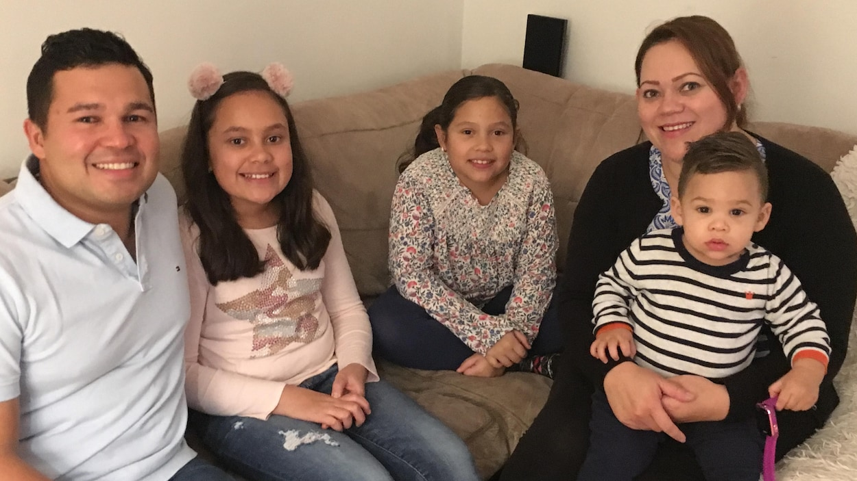 Deux adultes et trois enfants sont assis sur un canapé.