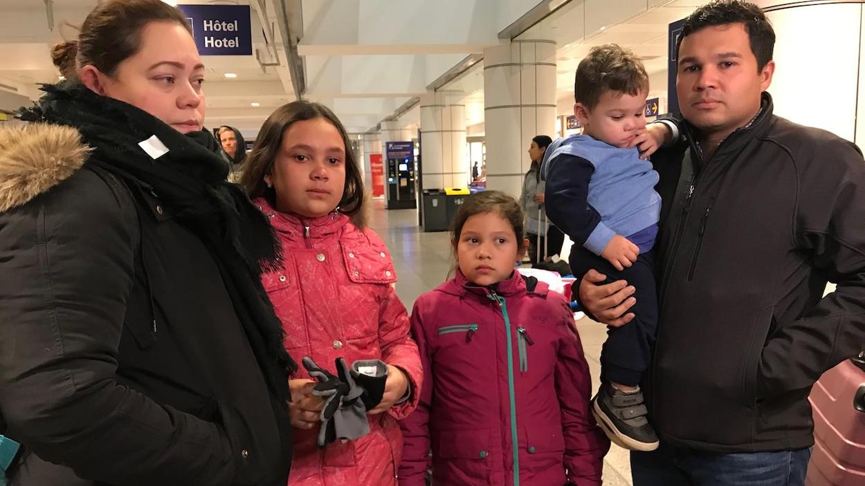 La famille, composée des parents et de trois enfants, le regard triste, attend de prendre l'avion à l'aéroport.