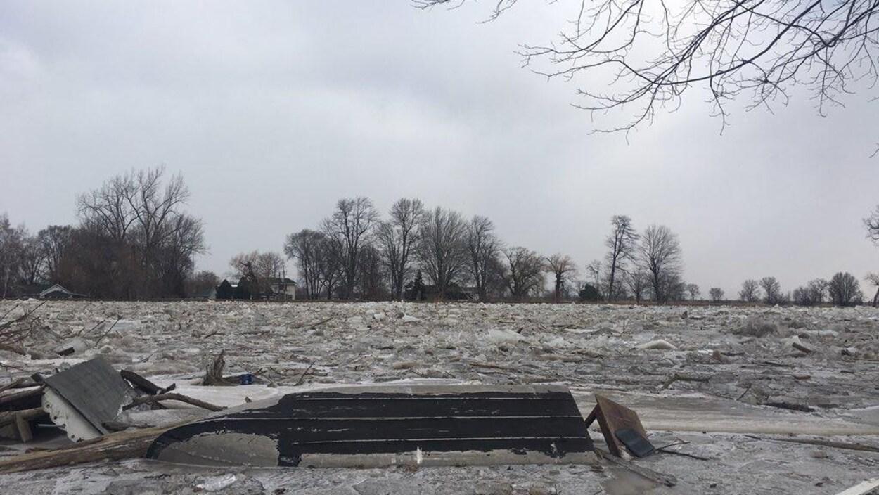 Un bateau et des débris transportés par une rivière qui sort de son lit.