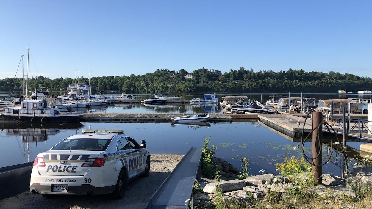 Une voiture du Service de police de la Ville de Gatineau est stationnée sur le quai d'embarquement de la marina.