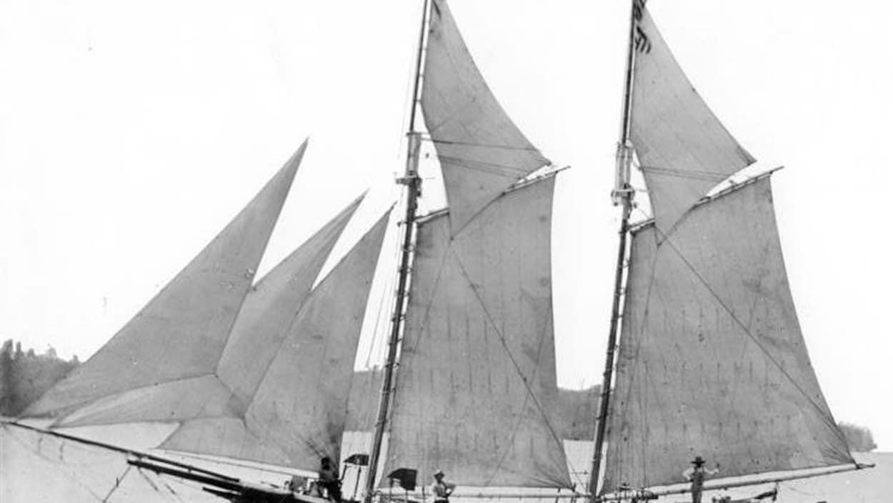 Vieille photo de grand bateau à voiles avec des gens sur le pont.