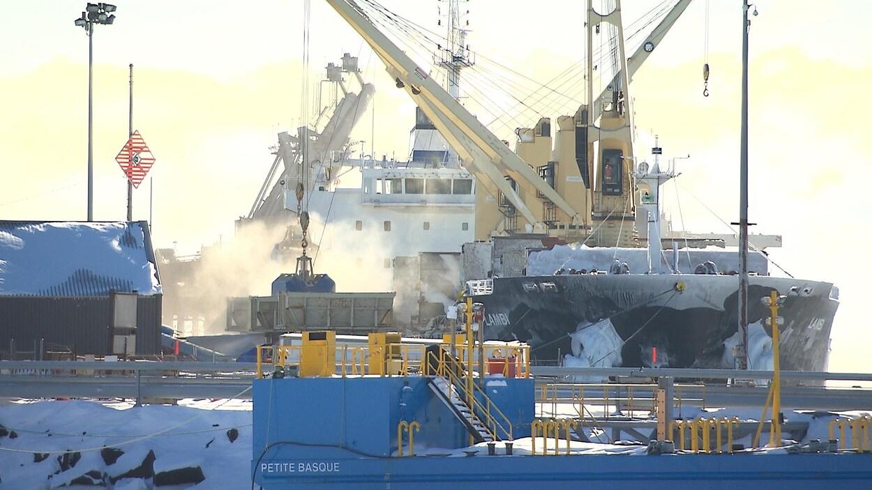 De la brume émane d'un bateau-cargo accosté au quai de Sept-Îles.