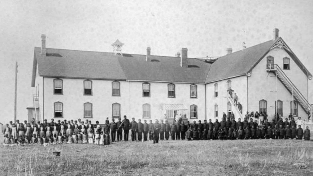 Des élèves debout devant le pensionnat autochtone Battleford Industrial School en 1895. Un édifice à deux étages.