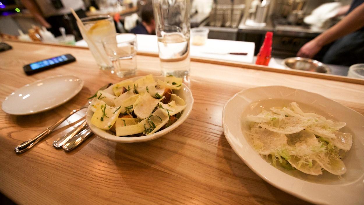 Deux plats sur le comptoir du restaurant Battuto: pieuvre sur un ragoût de lentilles au bouillon au lapin, pétoncles crus et rabioles.