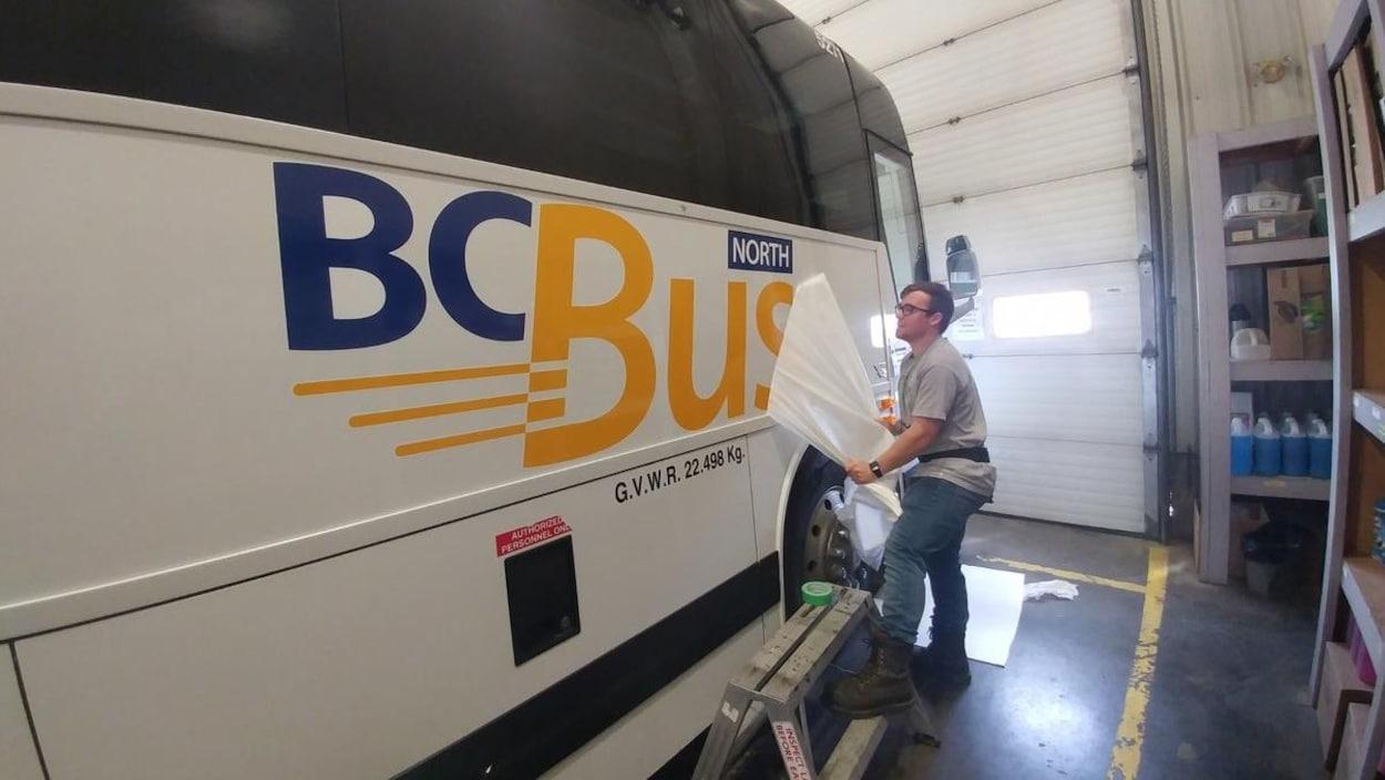 Un bus blanc avec de l'écriture en bleue et jaune.