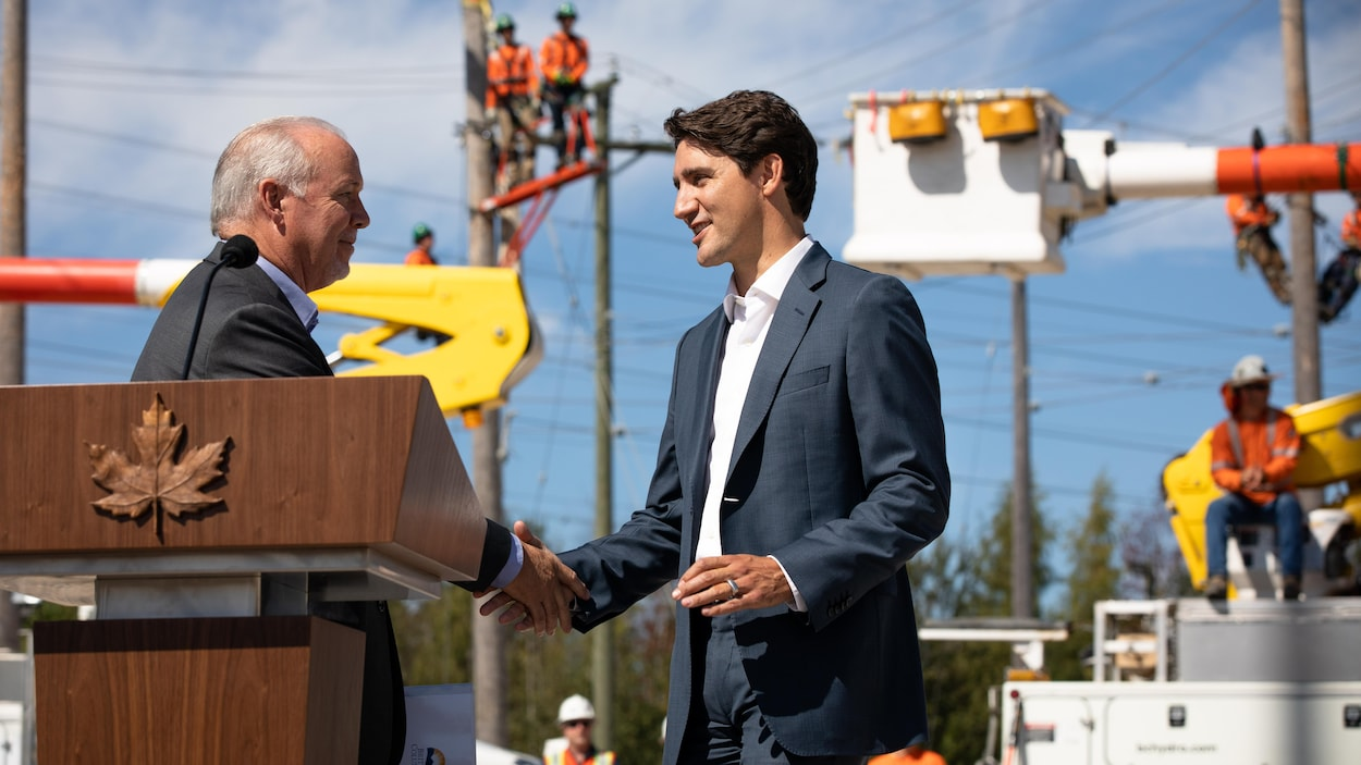 Justin Trudeau et John Horgan échangent une poignée de main devant des employés de BC Hydro, en arrière-plan.