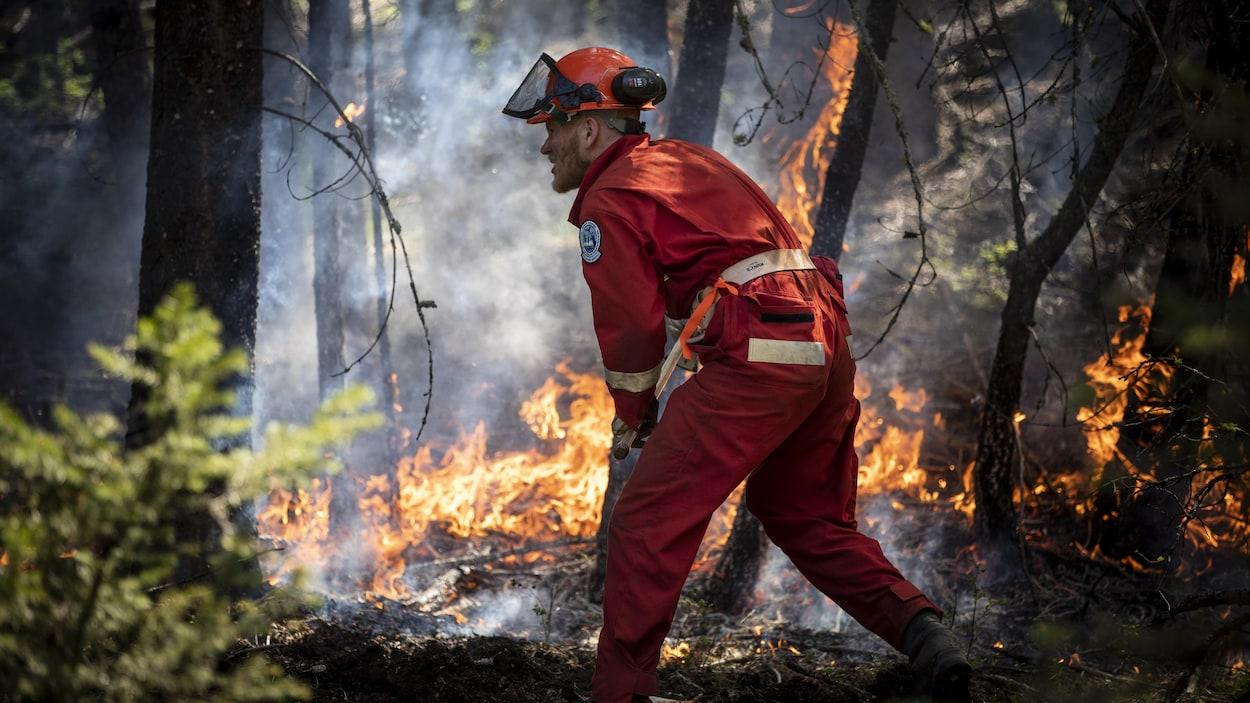 Un jeune pompier participe à un camp d'entraînement en forêt.